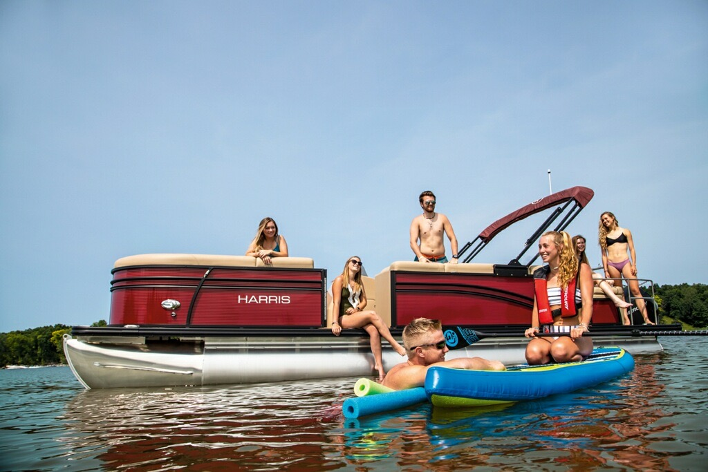 A red pontoon on a lake with a happy family having fun